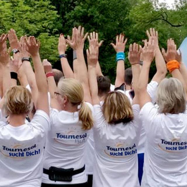 Eine Gruppe Mitarbeiter von hinten mit den Händen in der Luft